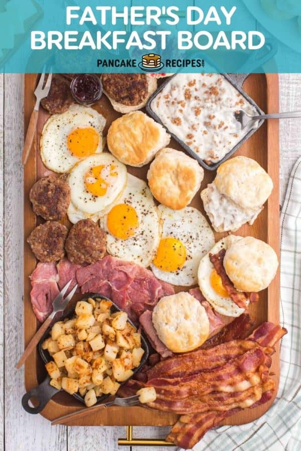 """Overhead view of a lot of breakfast food, text overlay reads """"father's day breakfast board."""""""