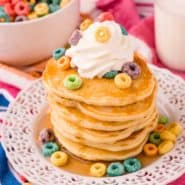 Tall stack of pancakes topped with whipped cream and froot loops cereal.