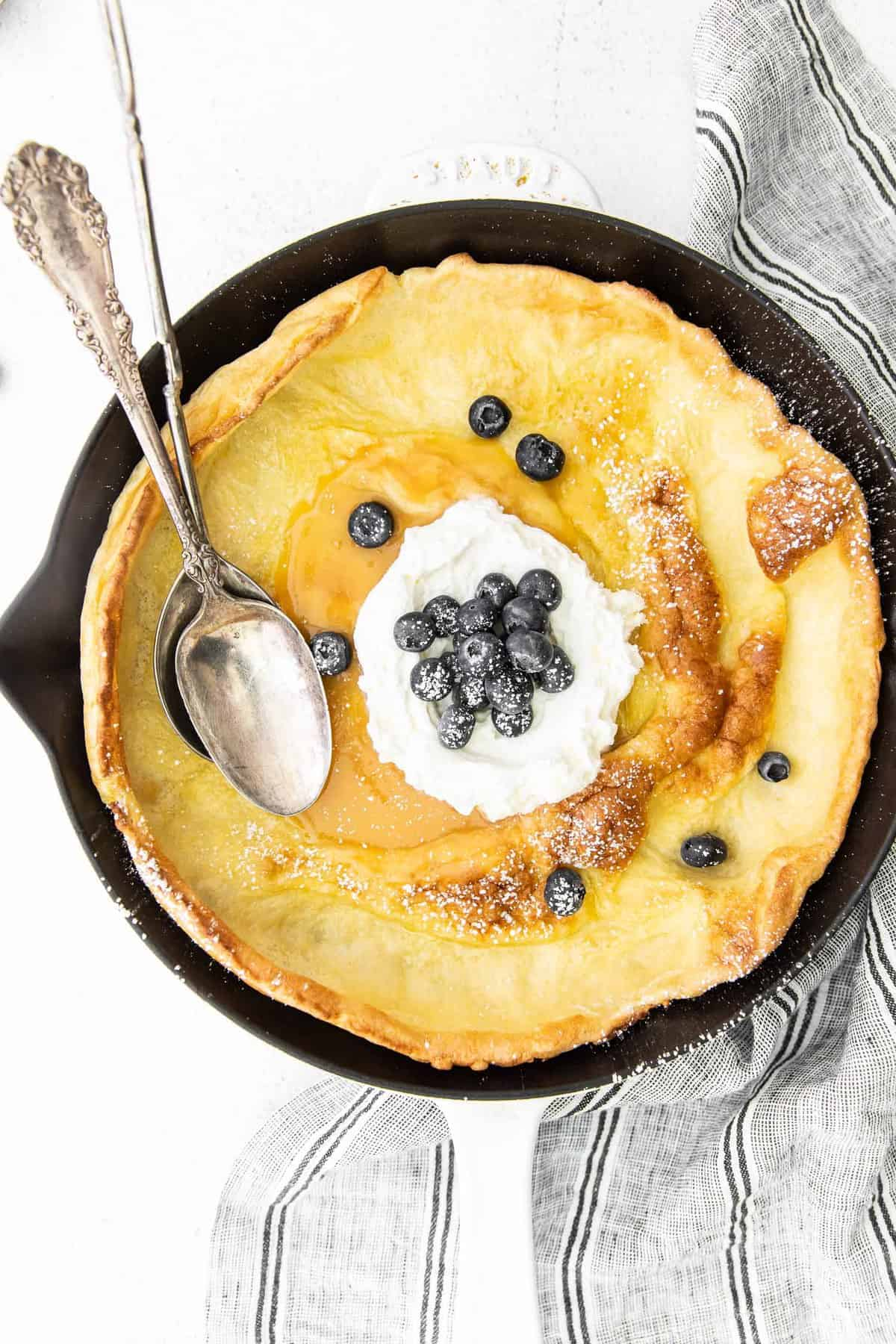 Overhead view of a lemon dutch baby pancake with blueberries and whipped cream.