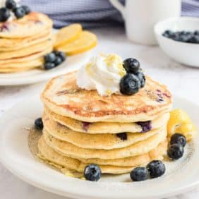 Stack of pancakes topped with whipped cream and blueberries.