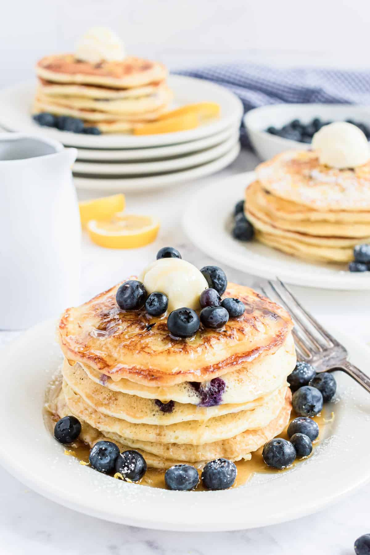 Stack of pancakes topped with scoop of butter, blueberries, and syrup.