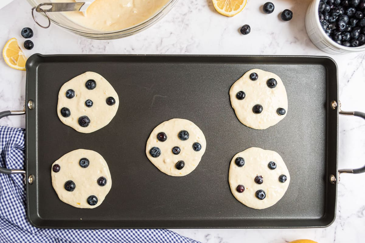 Uncooked pancakes on a black griddle.