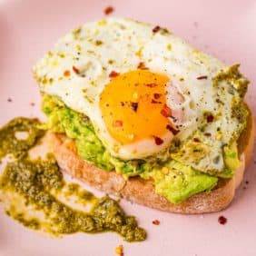 Pesto egg on top of avocado toast on a pink plate.
