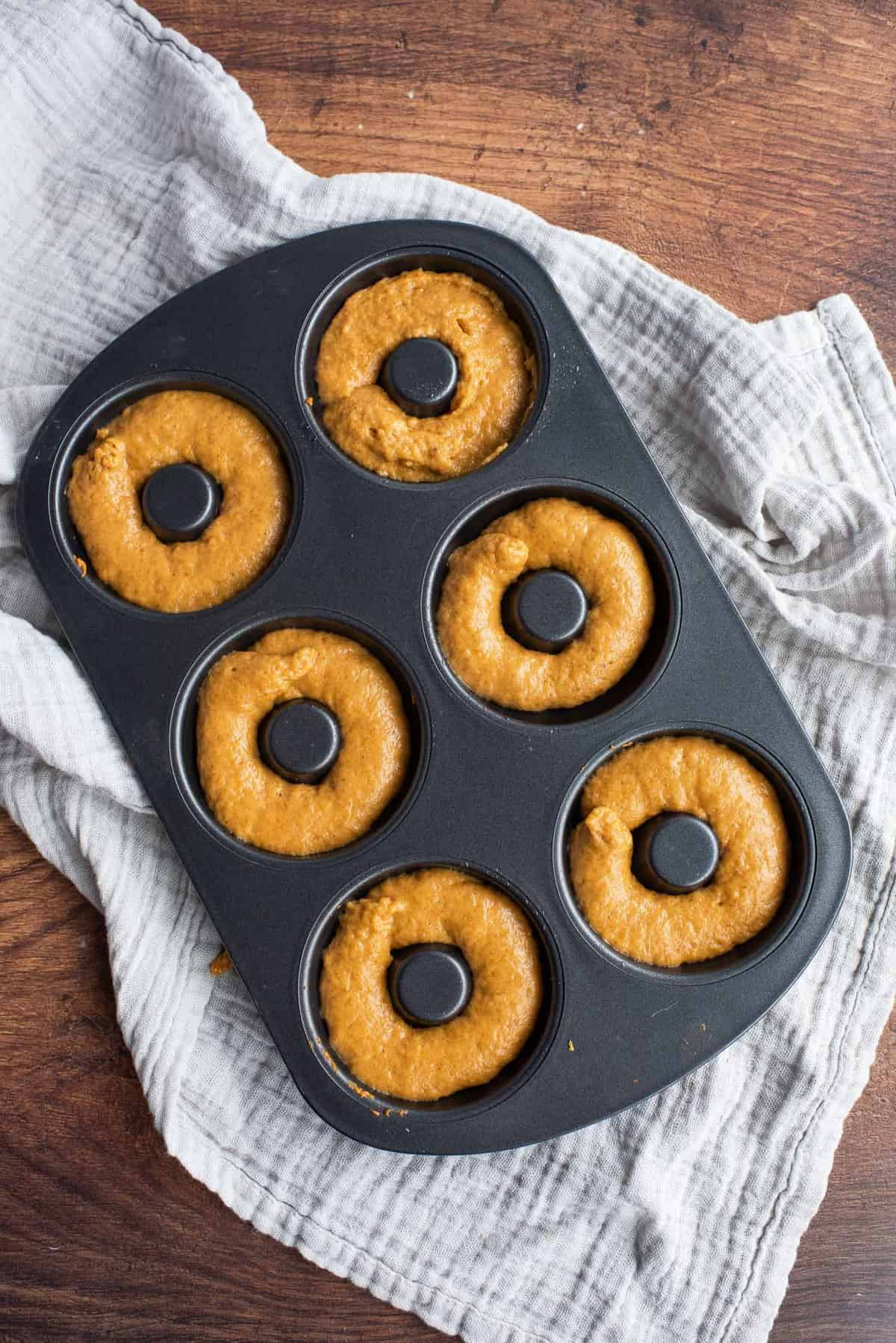 Unbaked pumpkin donuts in a black donut pan.
