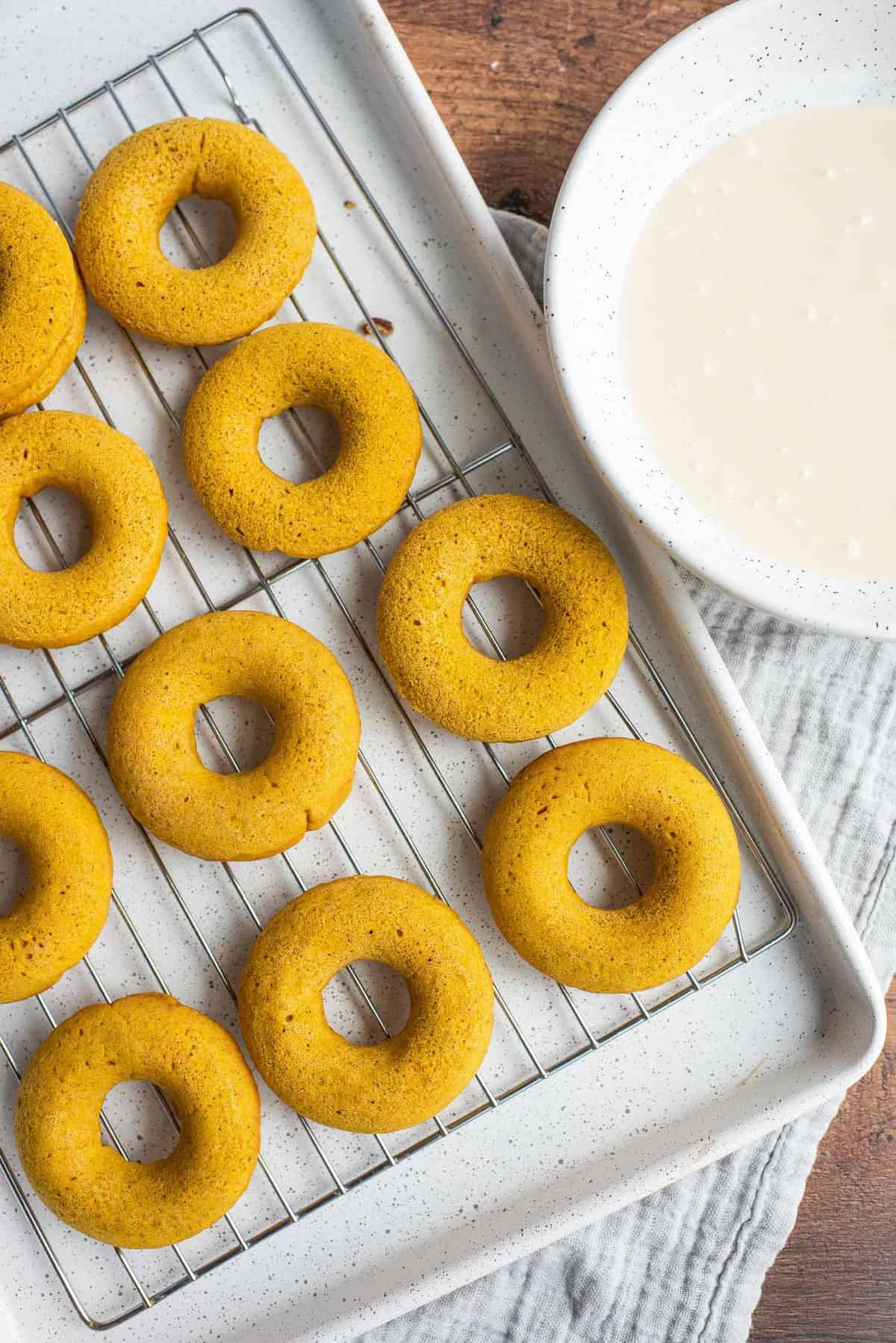 Baked donuts on a cooling rack, bowl of glaze next to it.