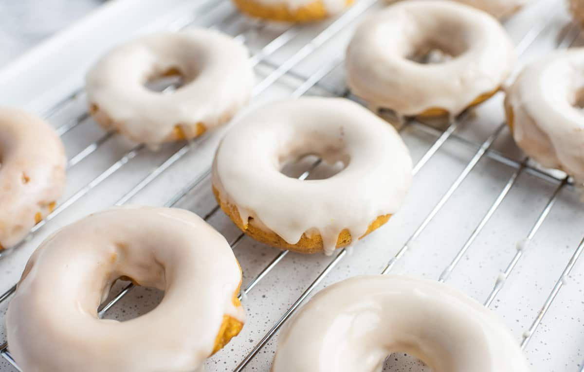 Pumpkin donuts on a cooling rack.