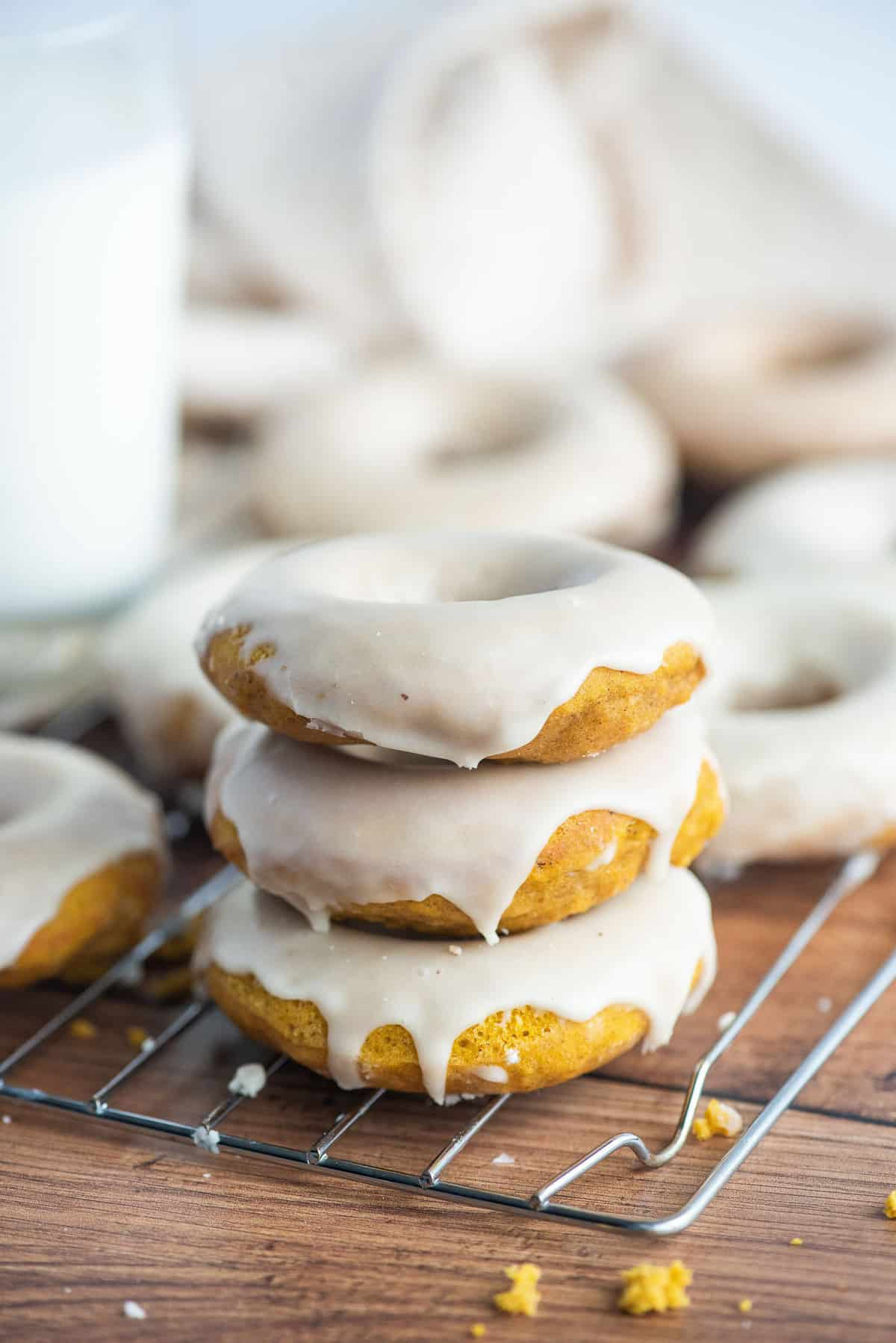 Three pumpkin donuts with glaze, more in the background.