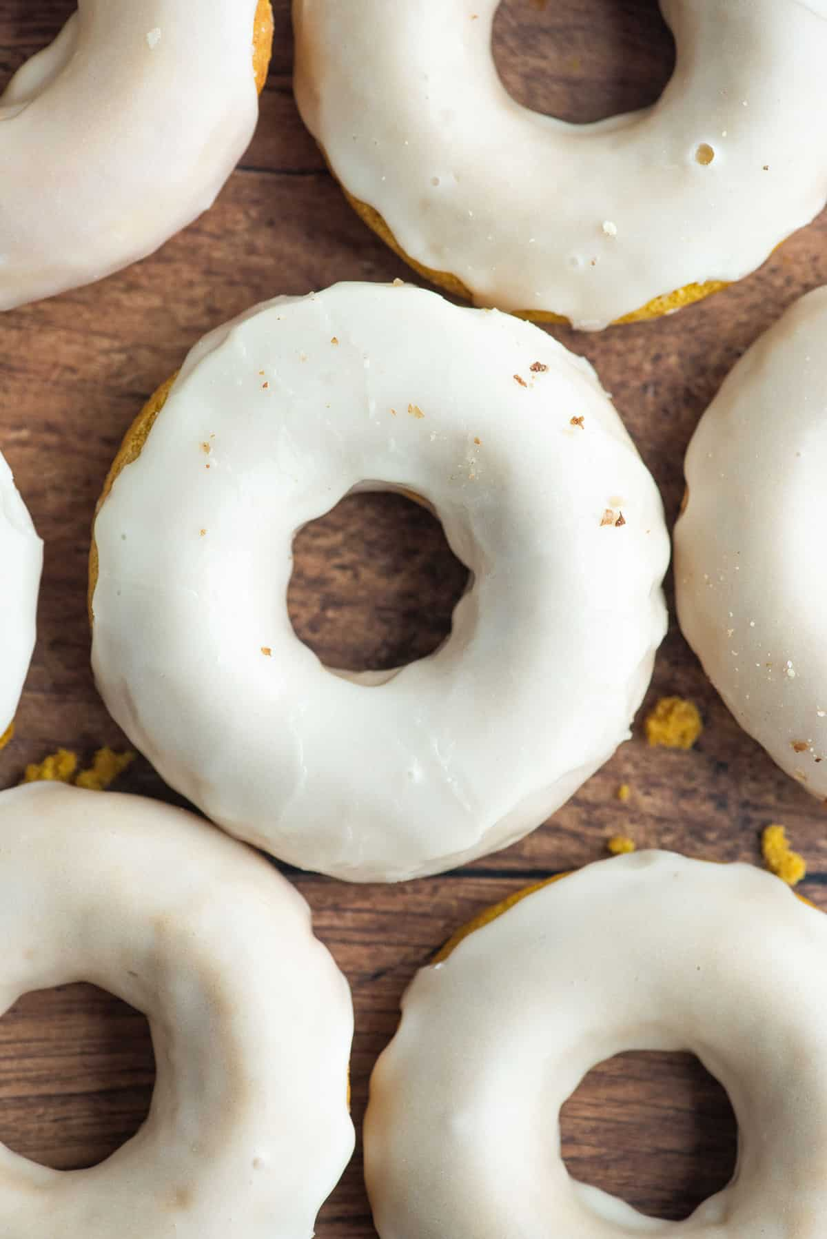 Overhead view of glazed donuts on a wooden surface.