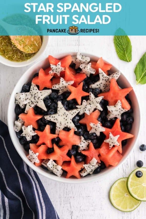 "Patriotic fruit salad with text overlay that reads ""star spangled fruit salad, pancakerecipes.com."""