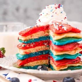 Red, white, and blue pancakes on a white plate, topped with whipped cream and sprinkles.