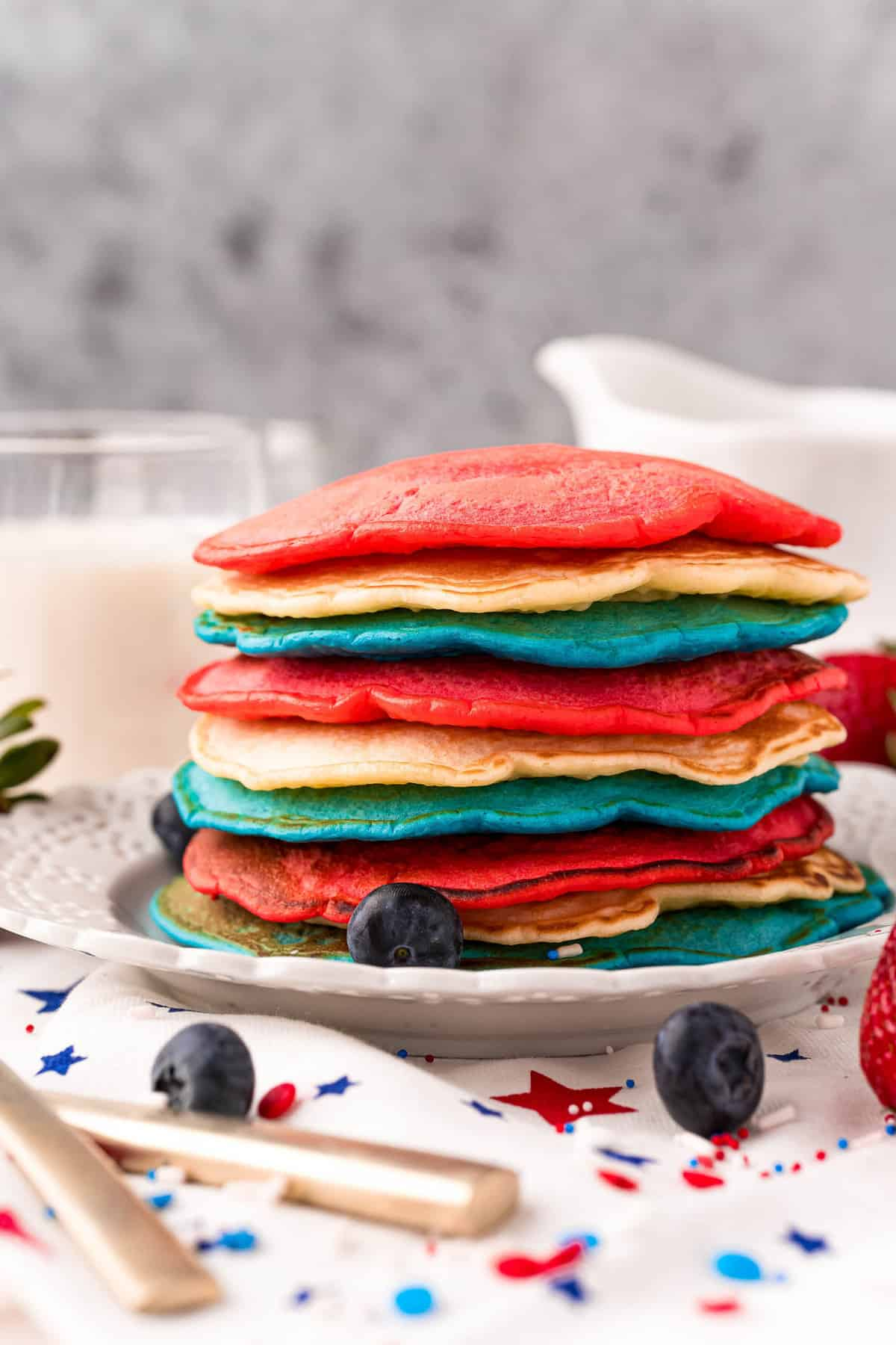 Patriotic pancakes with no toppings, stacked on a white plate.