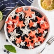 Fruit salad with red, white, and blue fruit cut into star shapes.