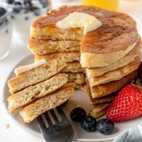 Stack of pancakes with a stack of three pieces on a fork.