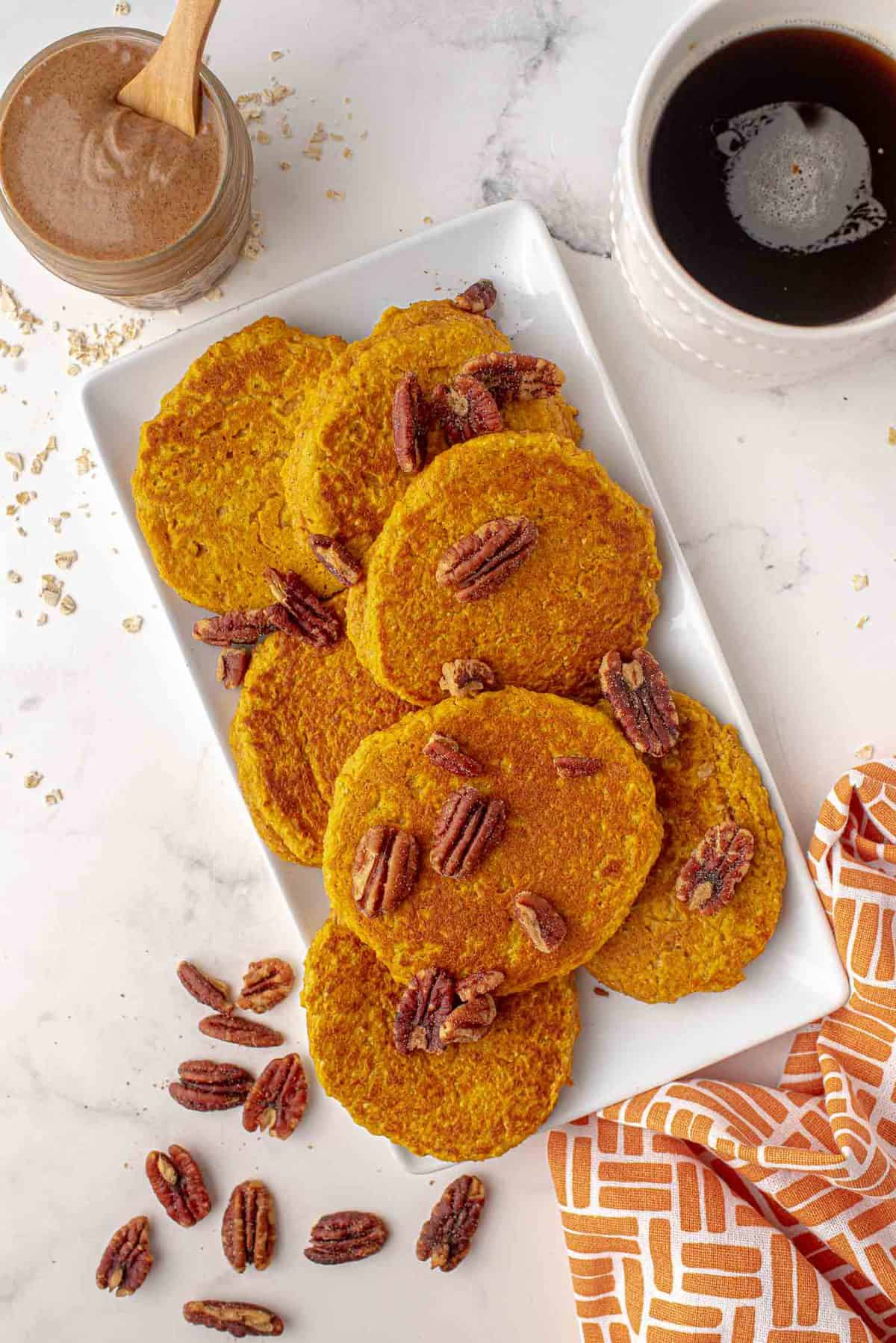Overhead view of healthy pumpkin pancakes on a platter sprinkled with pecans.