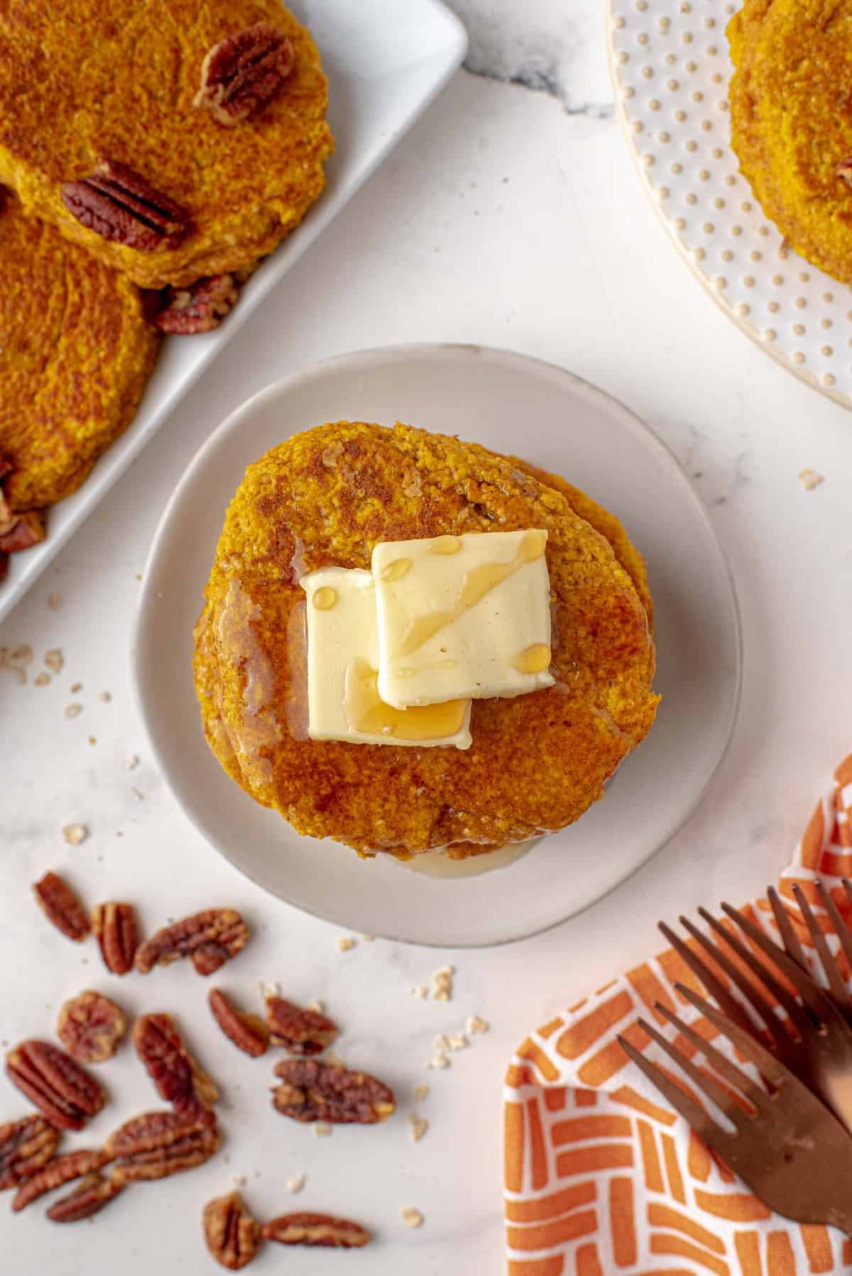 Overhead view of pumpkin pancakes with butter on top.