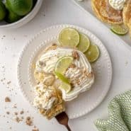 Overhead view of pancakes topped with whipped cream, lime, and graham crumbles.