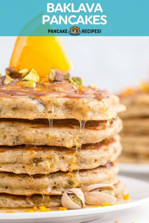 """Pancakes on a plate topped with an orange slice, text overlay reads """"baklava pancakes, pancakerecipes.com."""""""