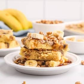 Stack of square cut pancakes, topped with walnuts, banana slices, and syrup.