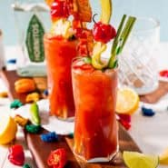Two bloody maria cocktails garnished with celery, pickles, bacon and more.