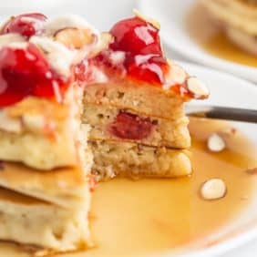 Cherry almond pancakes with a cut out to show texture.