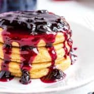 Stack of pancakes with blueberry sauce dripping down it.