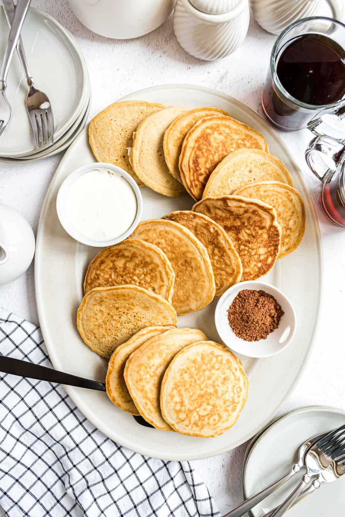 Pancakes on an oval white platter.