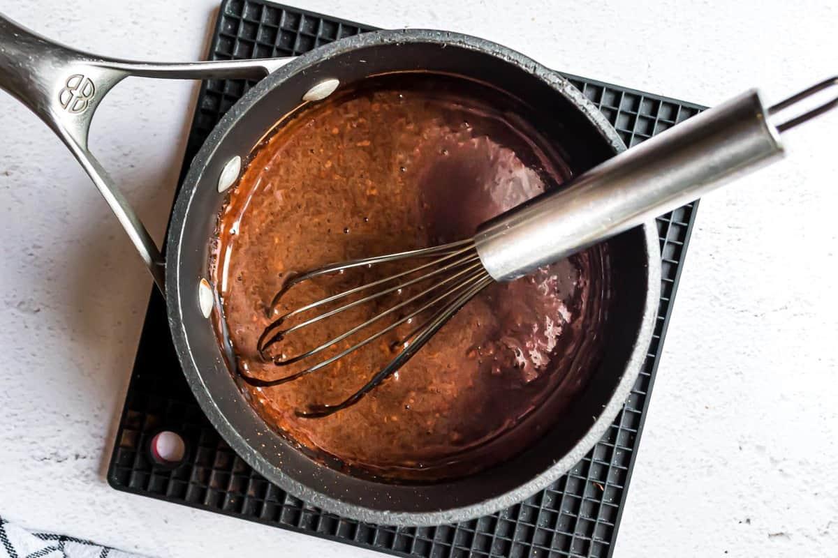 Kahlua syrup in a black saucepan.