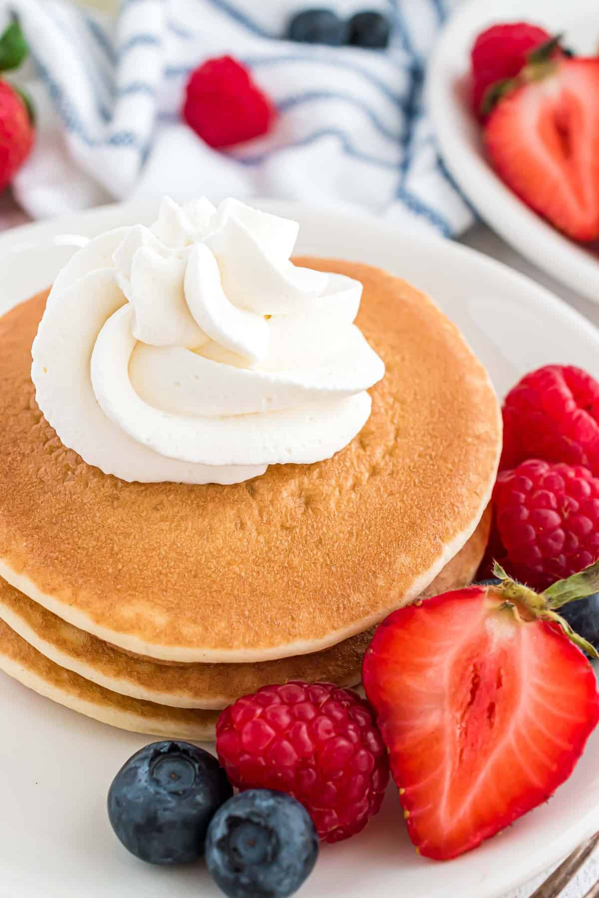 Whipped cream on a short stack of pancakes with fresh berries.