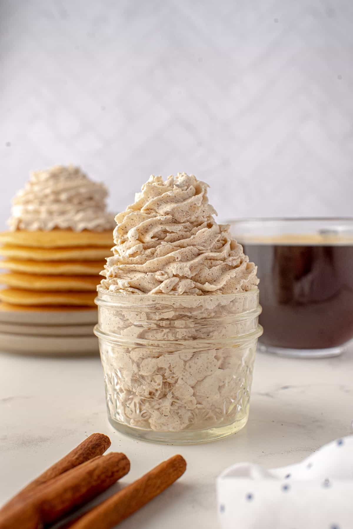 Cinnamon whipped cream piped into a jar, cinnamon sticks in foreground, pancakes in background.