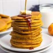 Stack of pumpkin pancakes being drizzled with maple syrup.