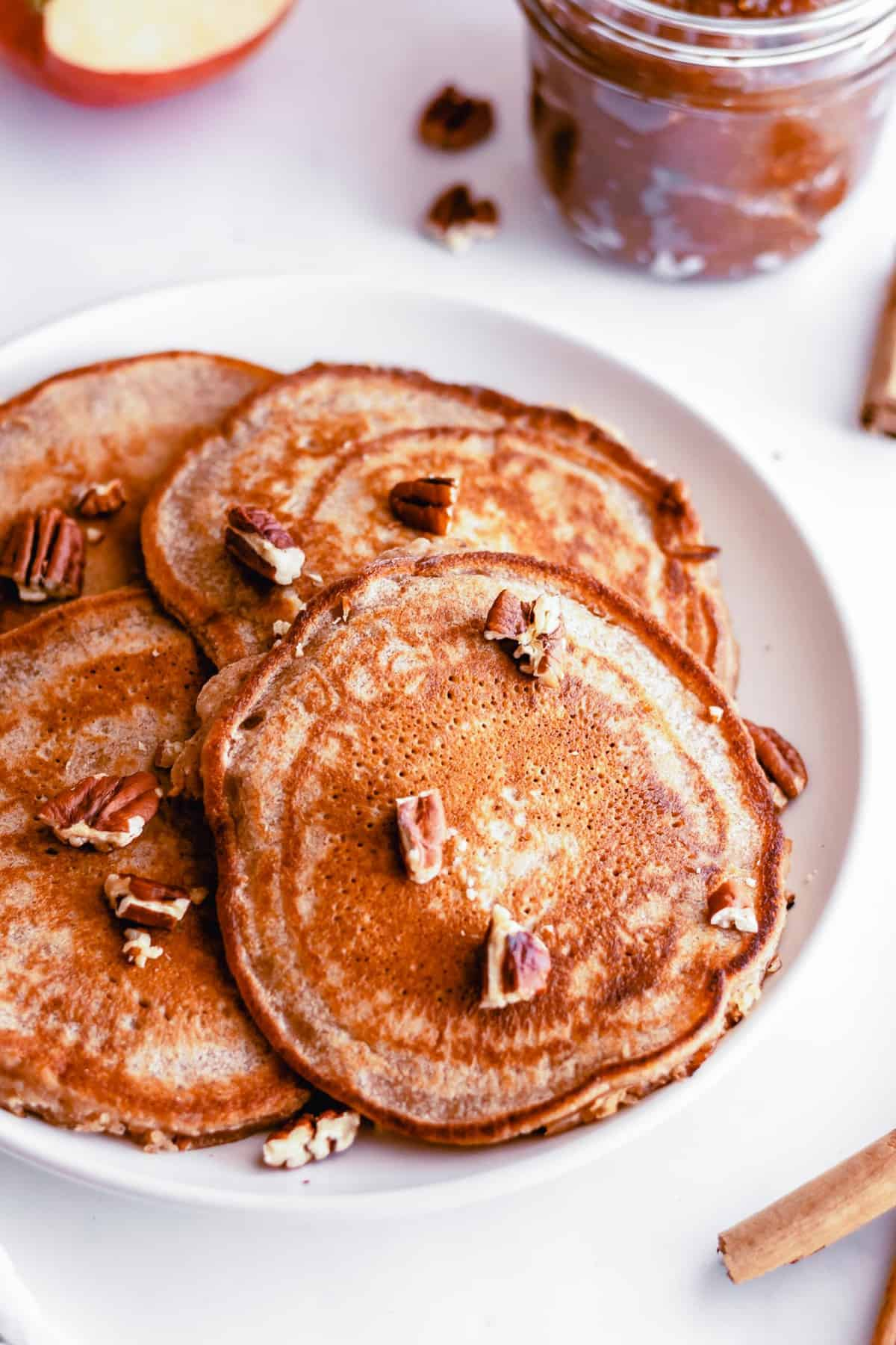 Pile of pancakes on a plate topped with pecans.