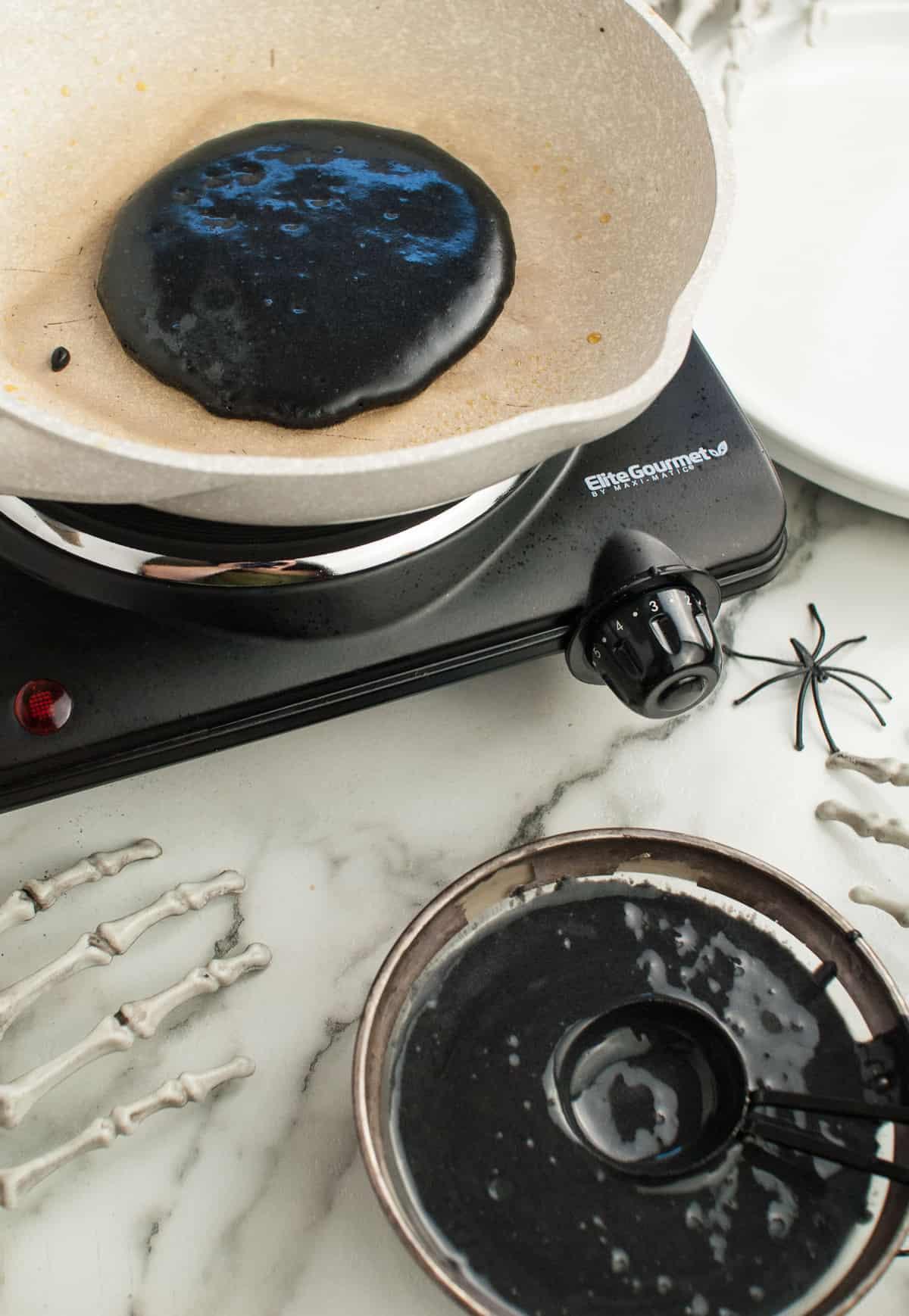 Black pancake batter in a skillet.