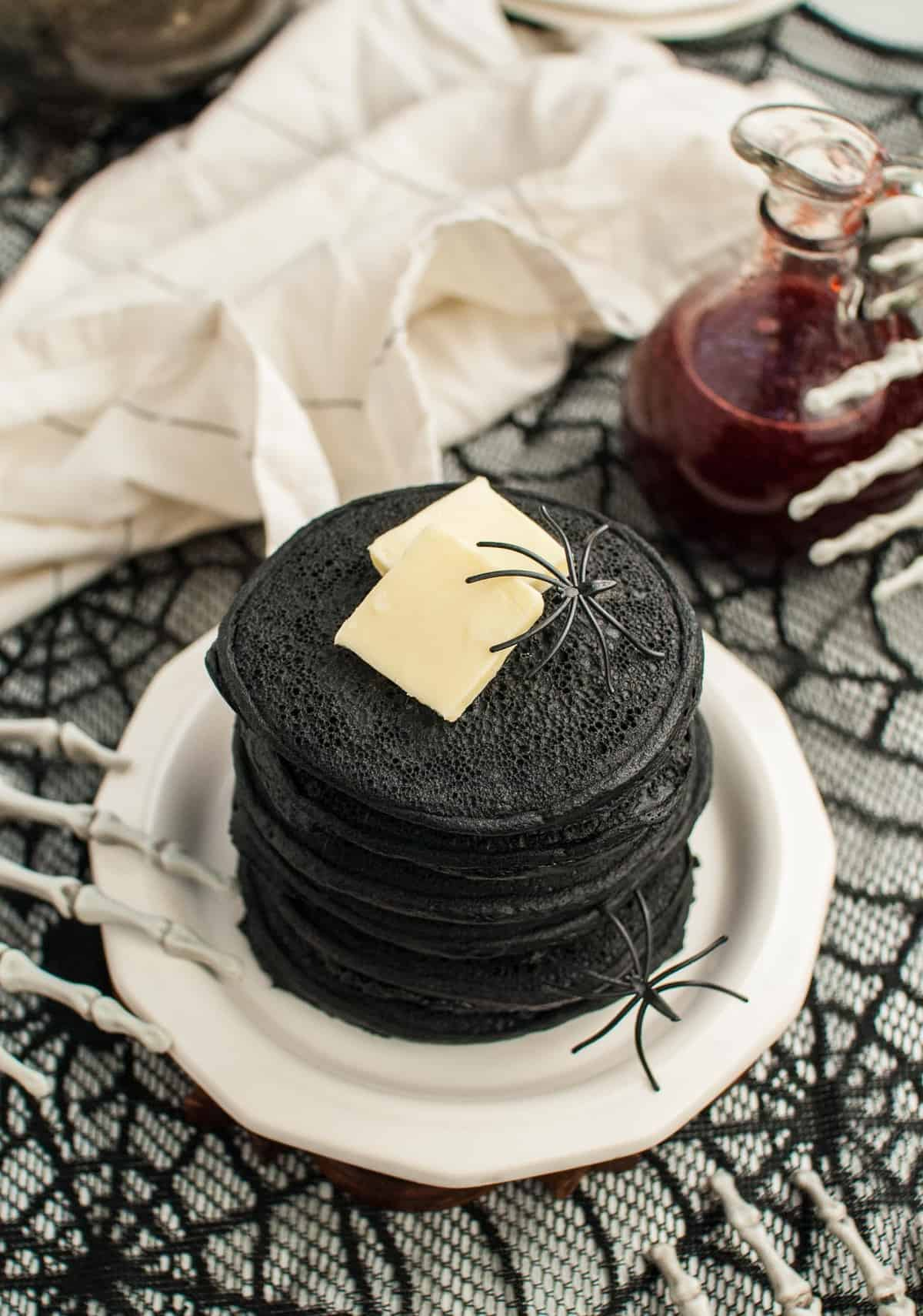 Dark black pancakes in a stack, topped with butter, surrounded by skeleton hands and fake spiders.