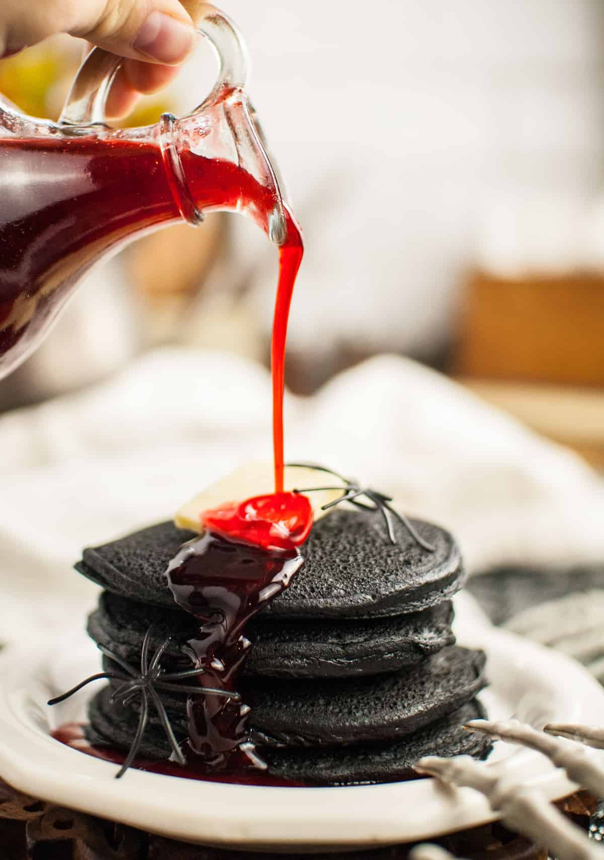 Red syrup being poured on a stack of black pancakes.