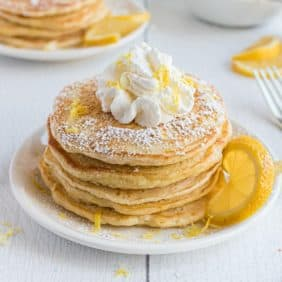 Stack of pancakes with whipped cream, powdered sugar, and lemon zest.