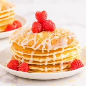 Stack of pancakes topped with fresh raspberries and lemon glaze.