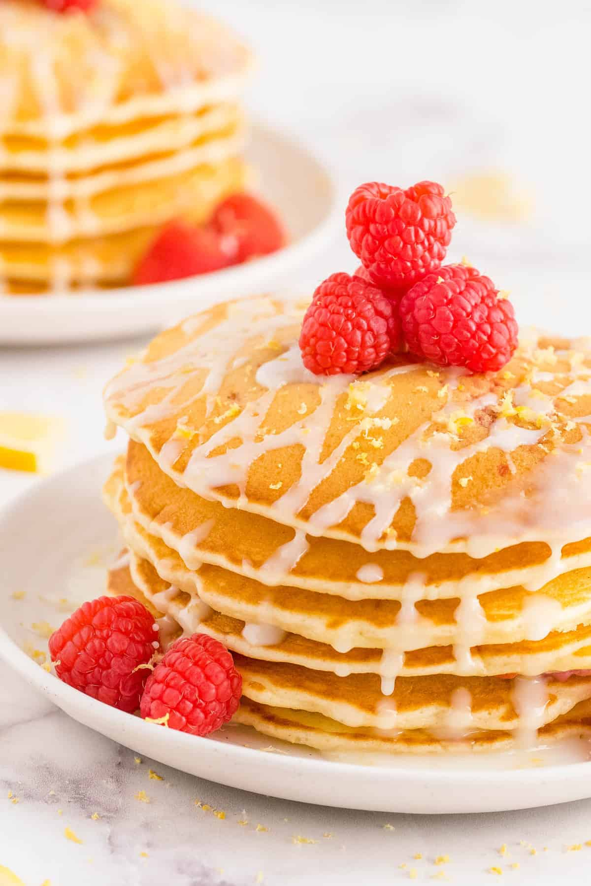 Stack of pancakes topped with fresh raspberries, lemon glaze, and lemon zest.