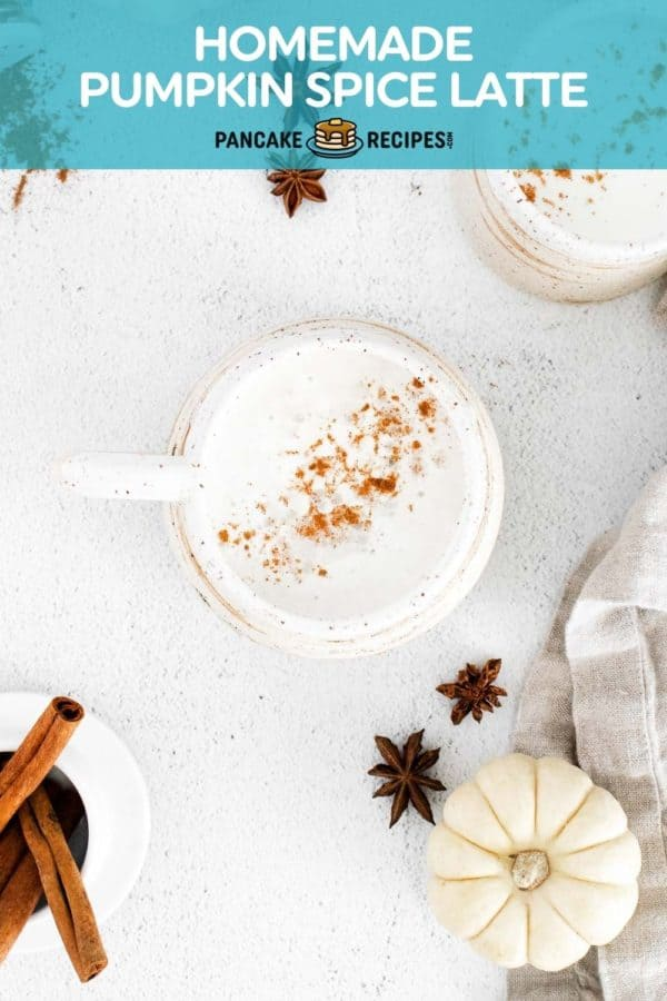 A latte in a white mug on a white background, sprinkled with a spice mixture including cinnamon.