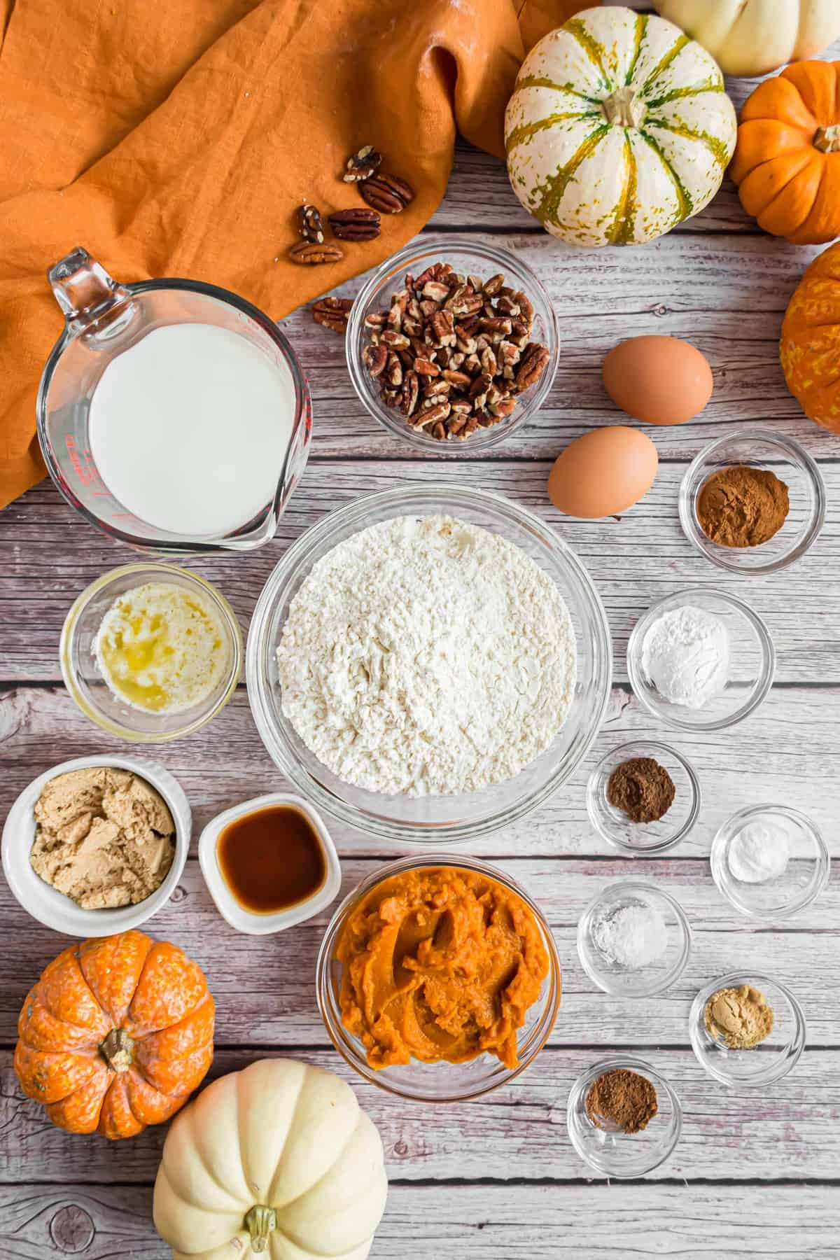 Ingredients needed to make pumpkin pancakes with pecan, most in clear glass bowls. Pumpkins also visible.