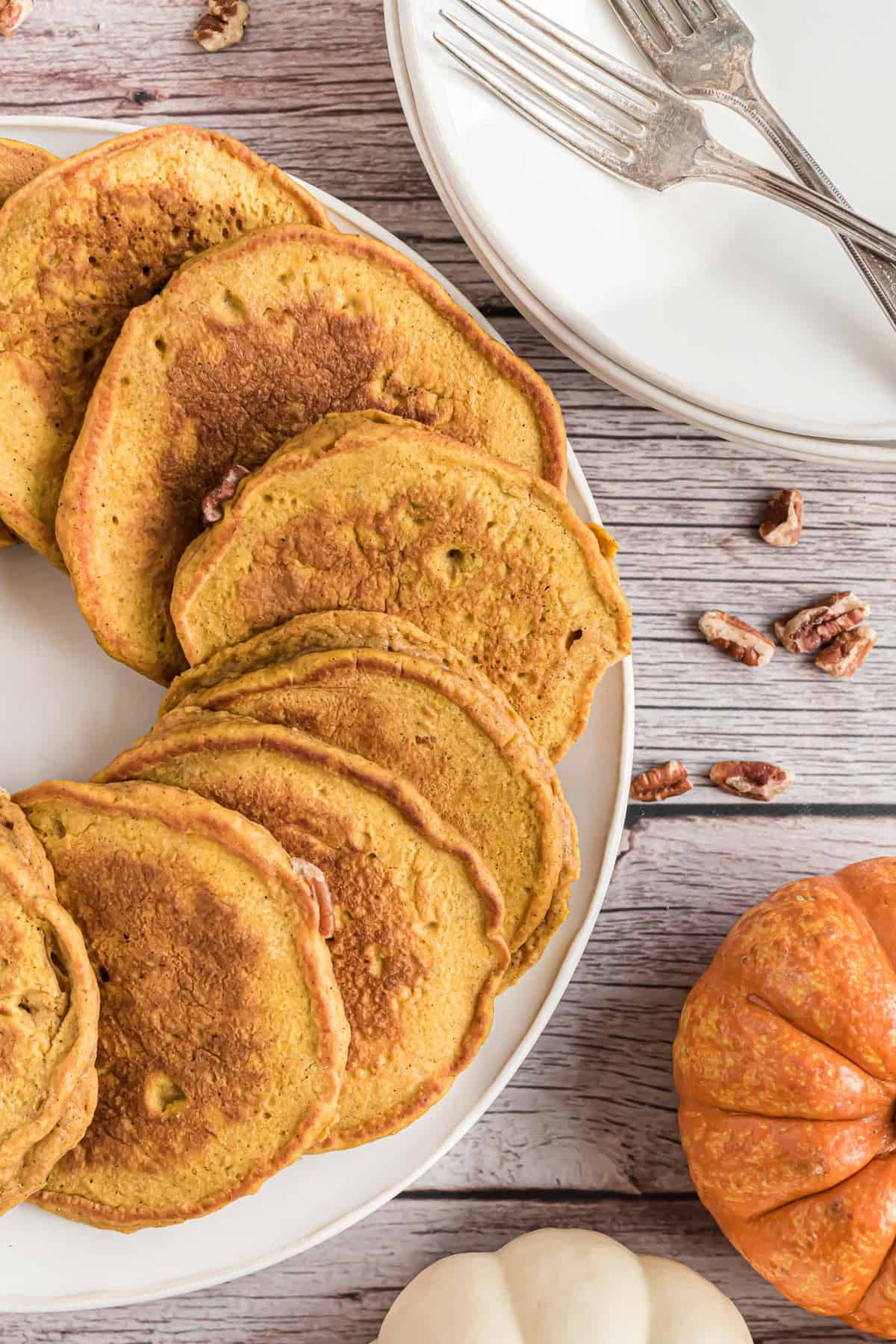 Pecan Pumpkin pancakes on a white plate, with pumpkins nearby.