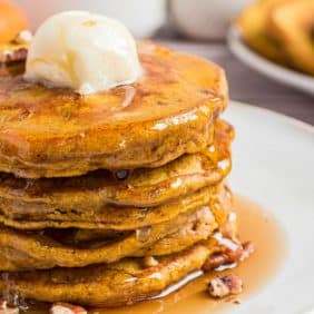 Close up of stack of pumpkin pancakes with a large ball of butter on top and maple syrup.