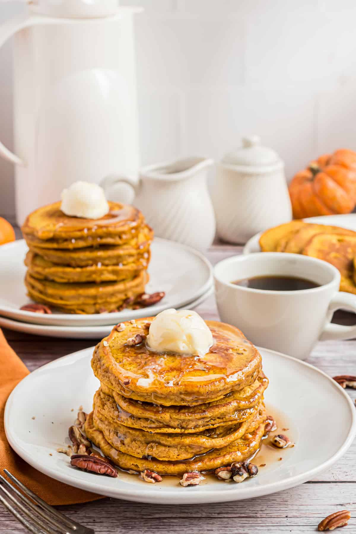 Two plates with large stacks of pumpkin pancakes.