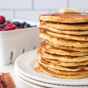 Stack of ricotta pancakes topped with a pat of butter and maple syrup.