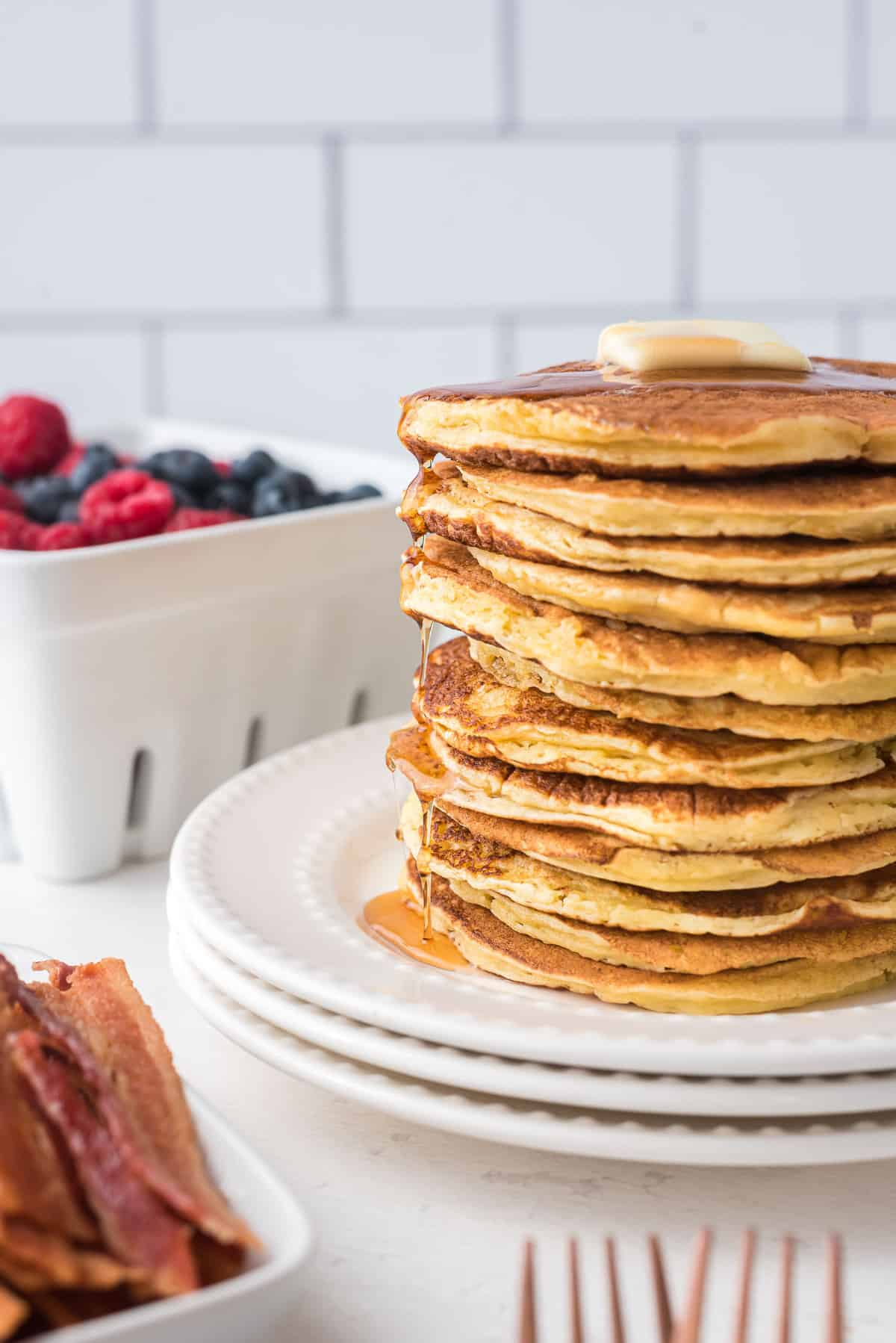 Very tall stack of pancakes topped with butter and dripping with maple syrup.