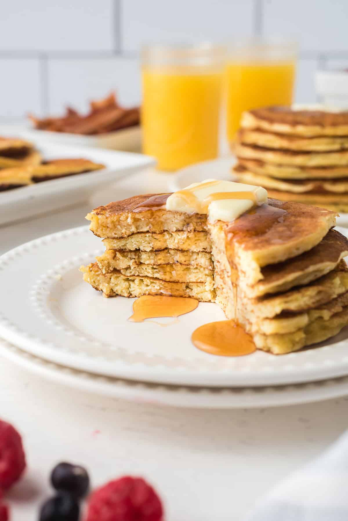 Cut stack of pancakes dripping with maple syrup.