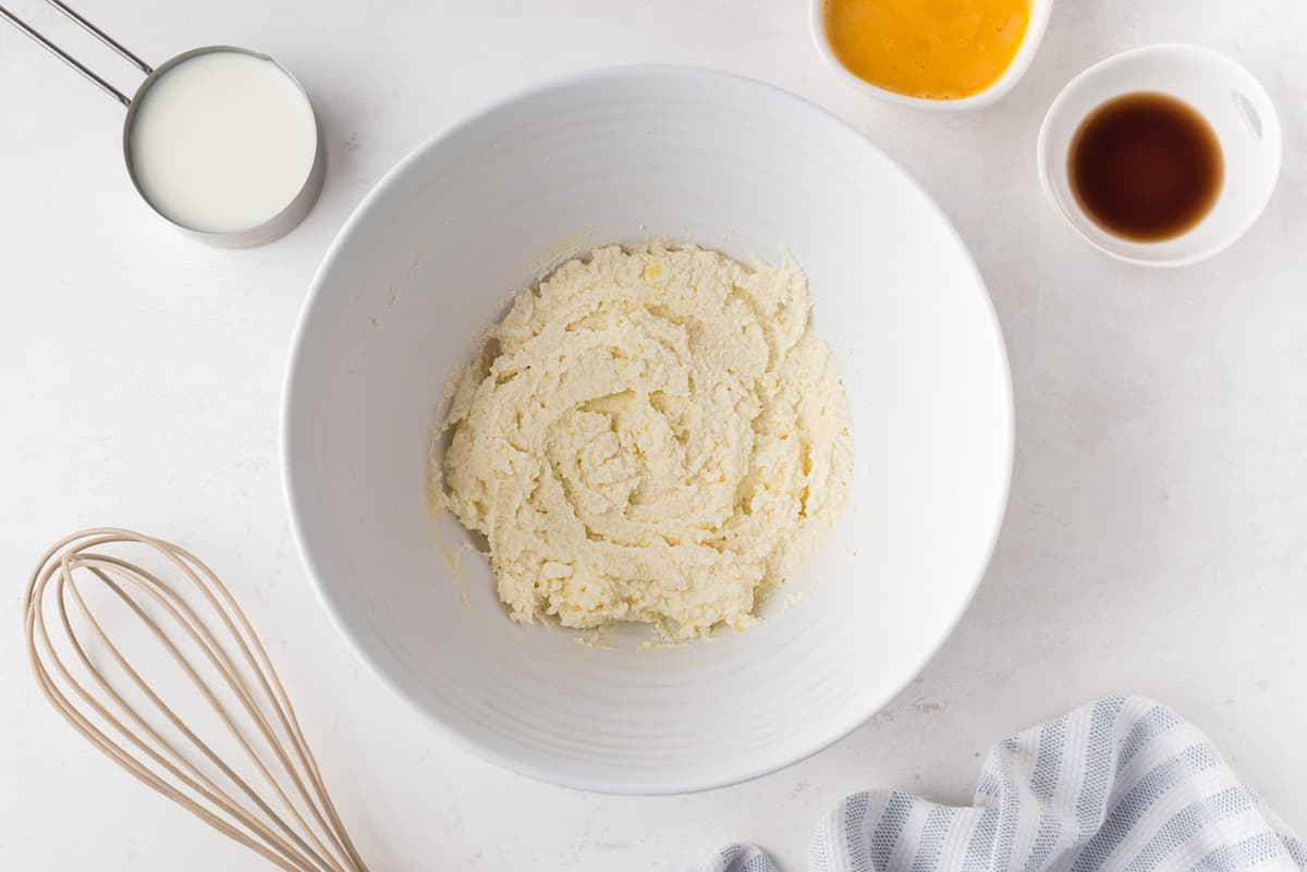 Ricotta and butter blended together in a white mixing bowl.