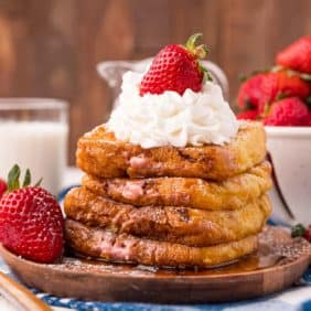 Stack of french toast stuffed with whipped cream and strawberries.