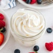 Whipped cream piped into a small jar, berries also visible.