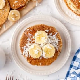 Overhead view of stack of pancakes topped with bananas and coconut.