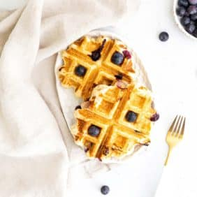 Two small waffles on a white background, topped with blueberries.